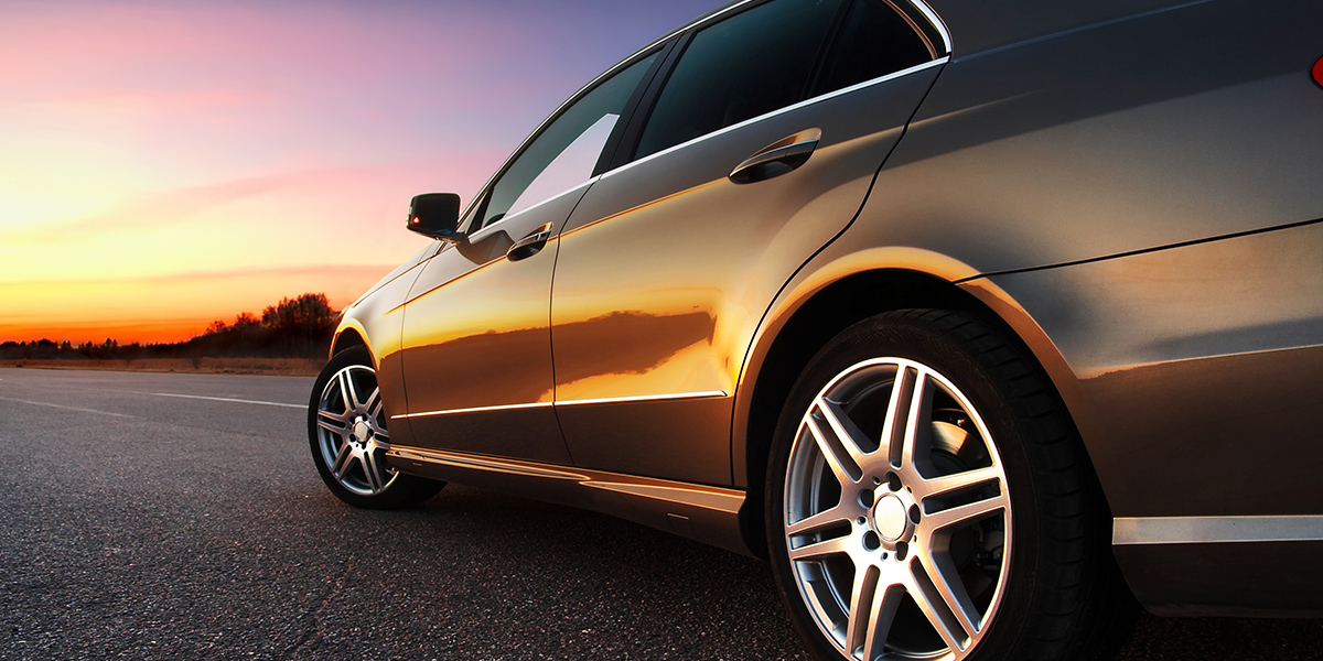Rear-side view of a luxury car on sunset car maintenance