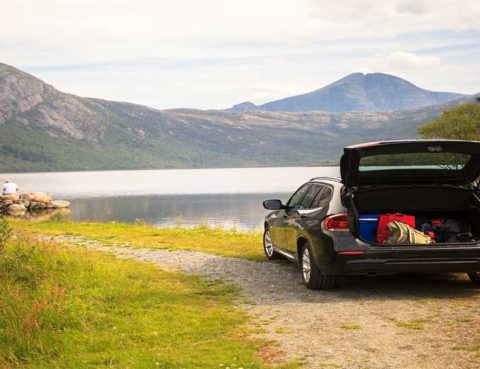 black hatchback with suitcases on a dirt road by a mountain lake