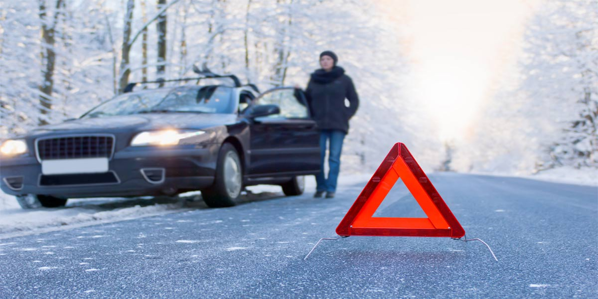 red caution sign on winter road with woman standing beside car stuck in ice
