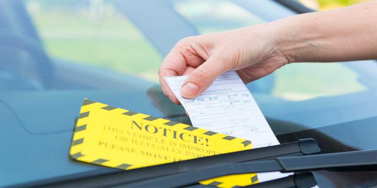 man's hand placing parking ticket under windshield wiper