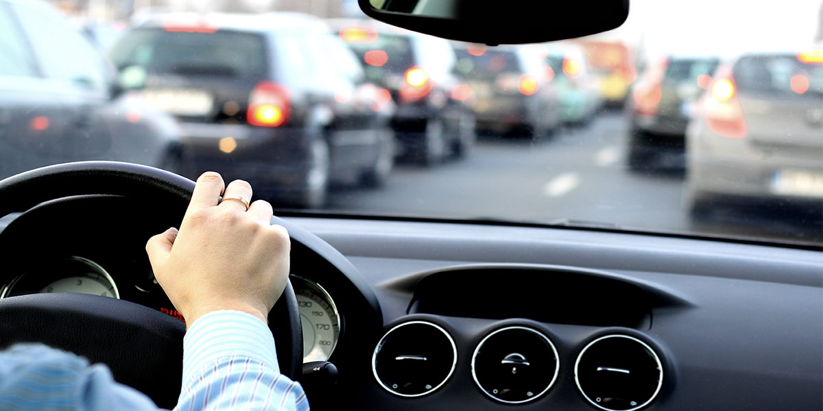arm of a driver on the steering wheel with bumper to bumper traffic in the background