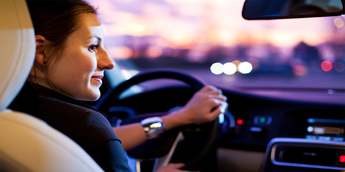 woman driving a car with black and tan interior with blurred landscape in the background