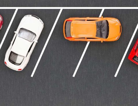 several cars parked properly with one car double parked