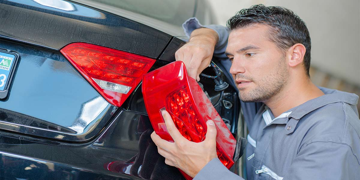 Man replacing tail light in auto shop