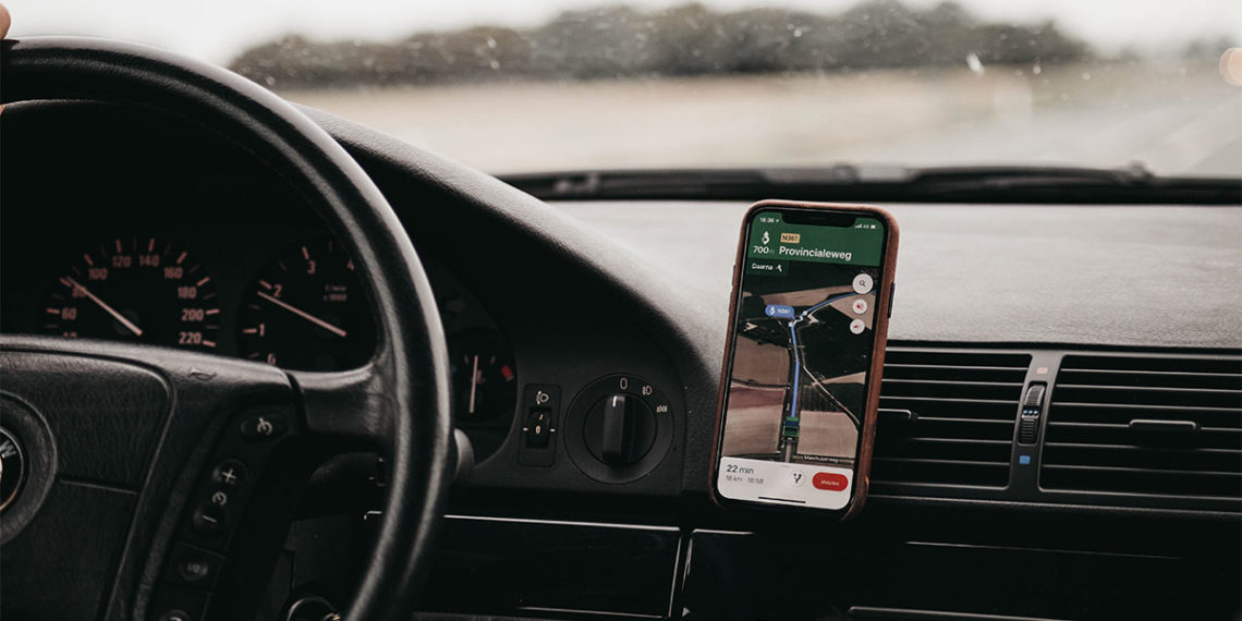 Interior of car with steering wheel and smartphone GPS mounted to the air vent
