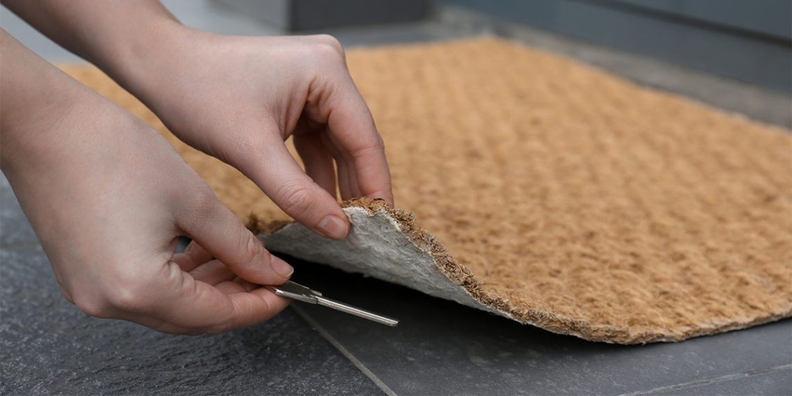hands lifting up doormat to hide a spare key underneath