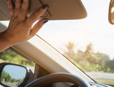 Driver holding up sun visor while driving a car