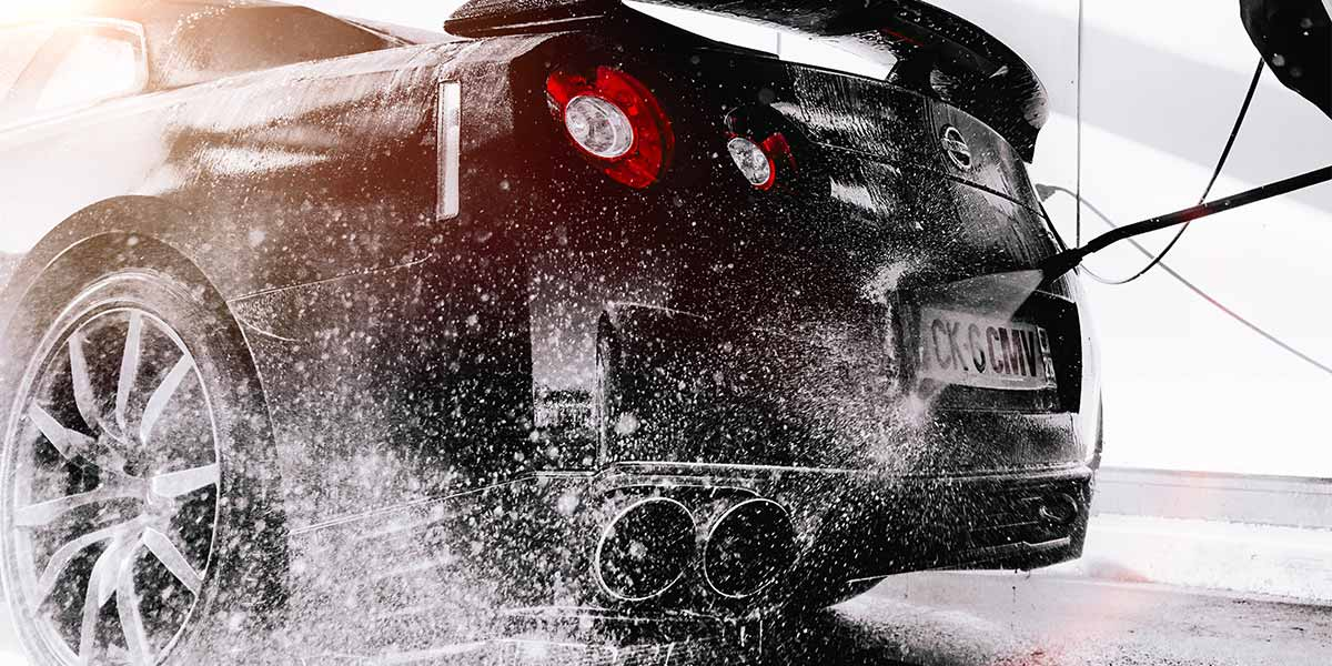 Black car being washed with a handheld pressure wand hose