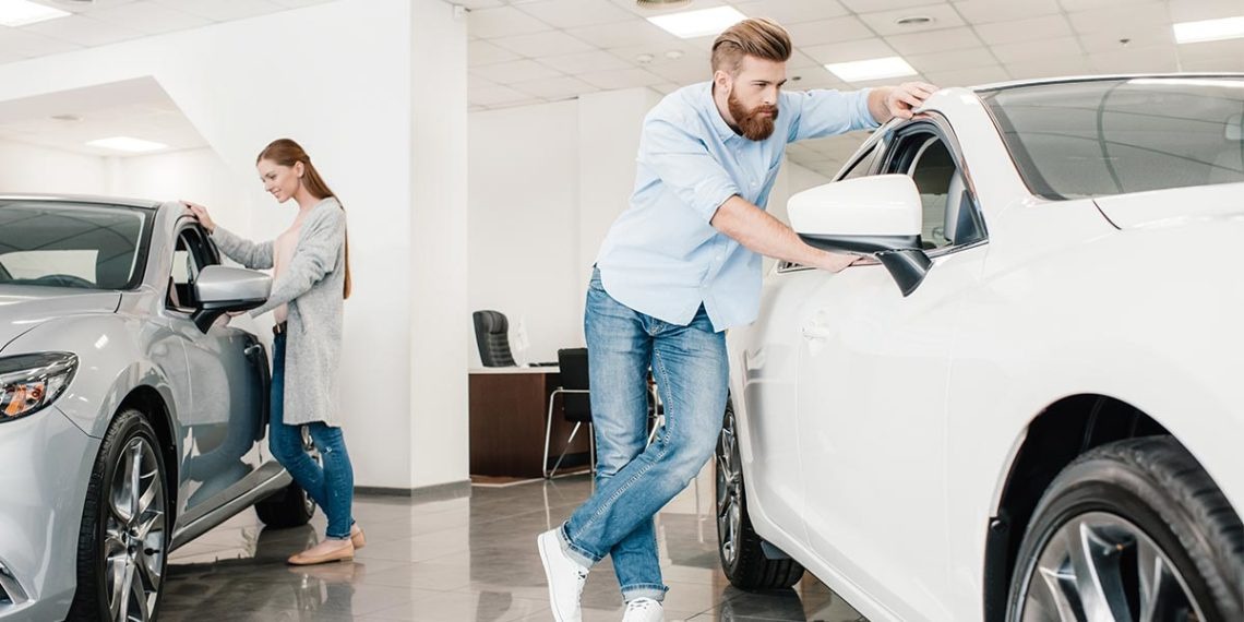 Young man and woman looking at two cars inside a car dealership