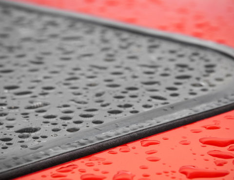 Roof of red car with sunroof covered in water droplets