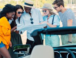 Group of friends standing in front of a car looking at a road map
