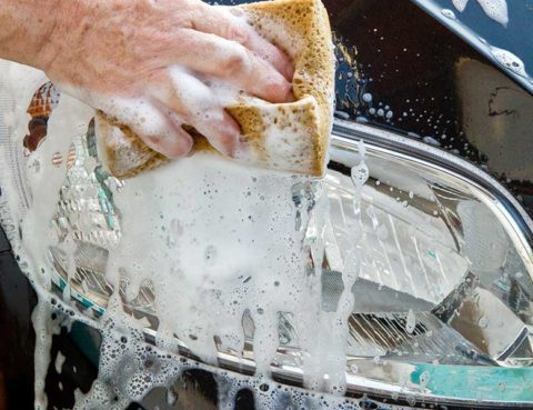 hand squeezing soap from a sponge onto a headlight