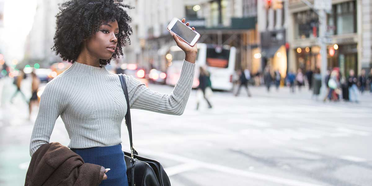Woman flagging a cab or rideshare car.