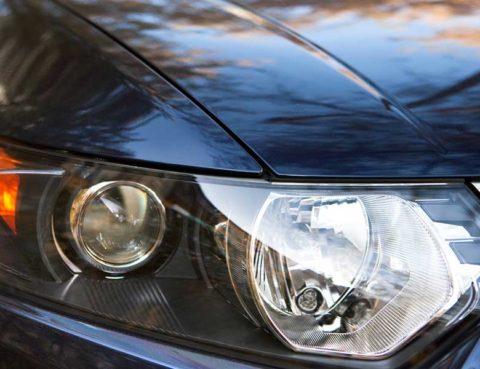 Up-close shot of a black car's passenger-side headlight.
